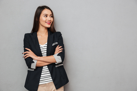 Smiling asian business woman with crossed arms looking away over gray background Banco de Imagens
