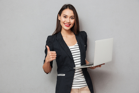 Holding asian business woman holding laptop computer and showing thumb up while looking at the camera over gray background