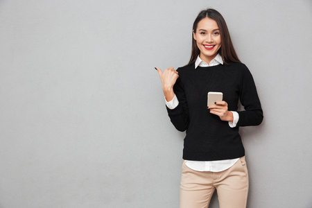 Lächelnde asiatische Frau in der Geschäftskleidung , die Smartphone hält und auf der Kamera beim Betrachten der Kamera über grauem Hintergrund zeigt
