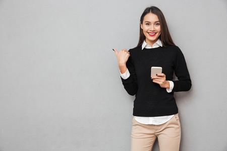 sourire femme asiatique dans des vêtements d & # 39 ; affaires tenant smartphone et pointant sur le mouvement tout en regardant la caméra sur fond gris