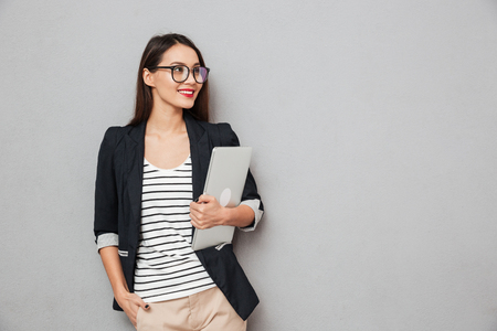 Smiling asian business woman in eyeglasses holding laptop computer over gray background