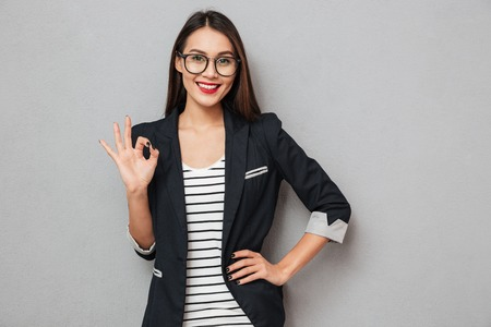 Smiling asian business woman in eyeglasses with arm on hip showing ok sign and looking at the camera over gray background