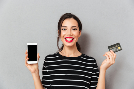 Portrait of a cheerful woman showing blank screen mobile phone and a credit card isolated over gray background