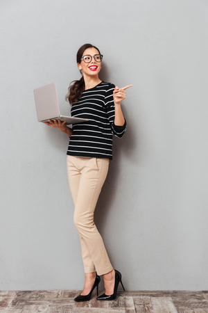 Full length portrait of a cheerful woman in eyeglasses holding laptop computer and pointing finger away at copy space isolated over gray background Stock fotó