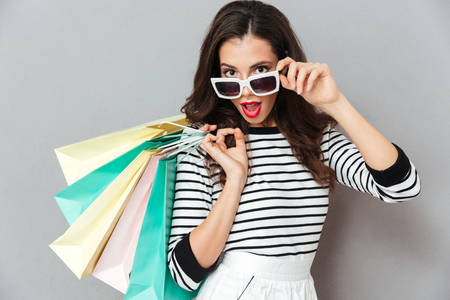 Portrait of a pretty flirty woman holding shopping bags and looking at camera isolated over gray background Stock Photo