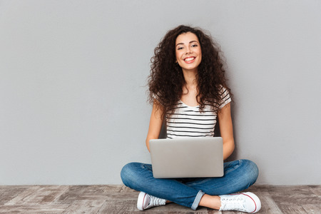 Portrait of satisfied female with beautiful smile enjoying watching movie in silver computer and sitting in lotus pose on the floor over grey wall Archivio Fotografico
