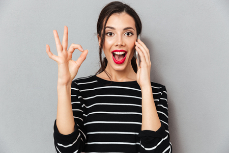 Portrait of an excited woman talking on mobile phone and showing ok gesture isolated over gray background