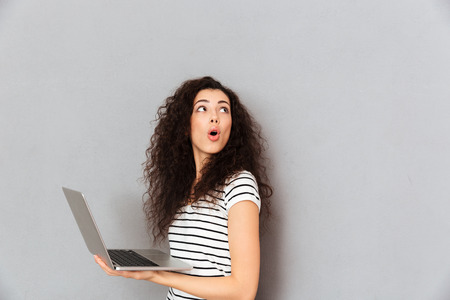 Lovely lady with curly hair posing with silver laptop being isolated over grey background turning around, and paying attention at something captivating