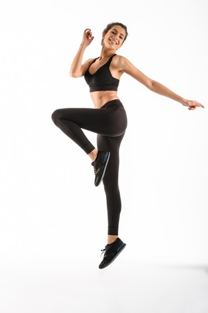 Full length image of Happy fitness woman jumping in studio and looking at the camera over white background Stock Photo
