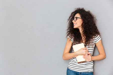 Portrait of smart smiling woman in eyeglasses holding books in hands being delighted to pass exams successfully, isolated over grey wall copy space Stock fotó