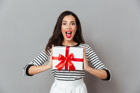 Portrait of a happy girl holding present box and looking at camera with mouth open isolated over gray background Stock Photo