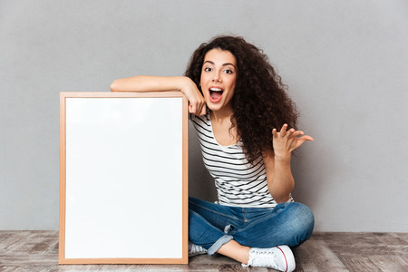 Young gorgeous female in jeans and t-shirt sitting in lotus pose on the floor with big great painting, feeling excitement over grey wall copy space Stock Photo
