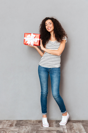 Full size picture of cheerful pretty woman holding gift-wrapped present with white bow being isolated over grey wall