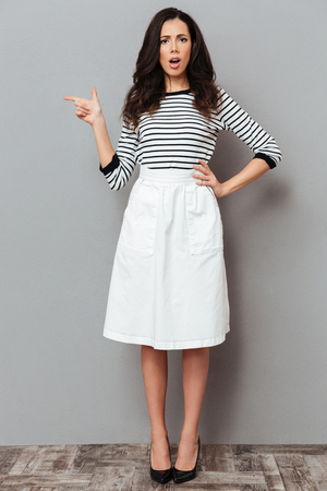 Full length portrait of a frowning woman dressed in a skirt standing and pointing finger away at copy space isolated over gray background