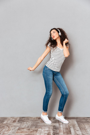 Full size view of charming young woman in striped t-shirt and jeans dancing, while listening melodies via headphones over grey background
