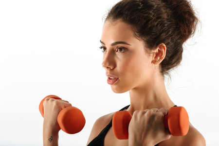 Close up image of curly brunette fitness woman doing exercise with dumbbells in studio over white background