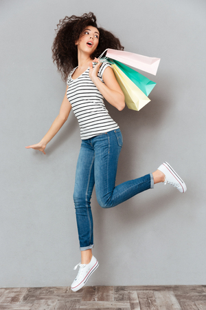 Caucasian brunette female in casual posing on camera with a lot of packages in hand, being satisfied after shopping over grey wall in studio