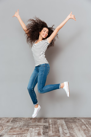 Joyous brunette female in casual posing on camera jumping, with hands throwing up in air over grey wall in studio