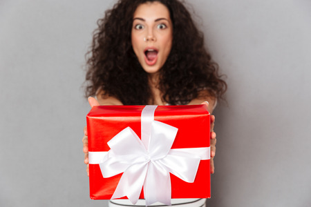 Brunette happy woman in defocus posing against grey wall holding red box gift-wrapped with white bow, showing it on camera Banco de Imagens