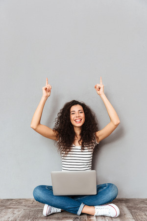 Picture of agitated woman sitting with legs crossed on the floor being happy and excited, putting index fingers in the air over grey wall Stock Photo