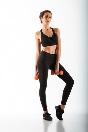 Full length image of beauty fitness woman posing with dumbbells and looking at the camera over white background Stock Photo
