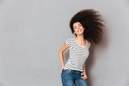 Gorgeous woman in striped t-shirt having fun with waving her beautiful hair smiling on camera being joyous and happy, over grey wall
