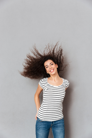 Cheerful brunette female in casual posing on camera with sincere smile shaking her hair while being in good mood, over grey wall