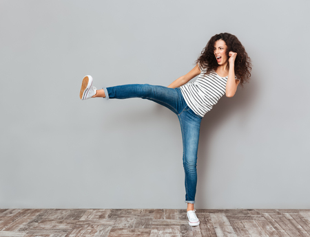 Portrait of strong young female with curly brown hair kicking invisible opponent, punching with leg over grey wall Stock Photo