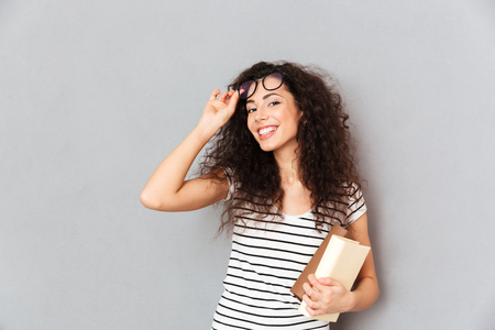 Young female teacher in eyeglasses with curly hair standing with books in hand over grey wall enjoying her work in college, being clever and intellectual