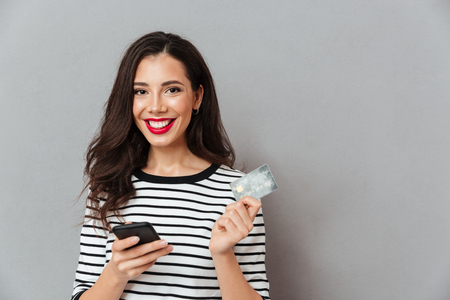 Portrait of a happy girl holding mobile phone and a credit card isolated over gray background Stockfoto