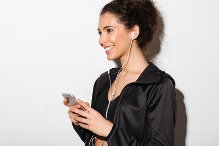 Side view of cheerful curly brunette fitness woman listening music and holding smartphone while looking away over white background