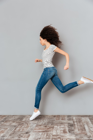 Vivacious and self-motivated woman in striped t-shirt and jeans, running along grey wall feeling strength
