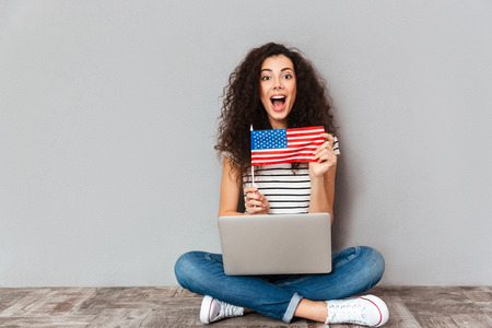 Gorgeous female with beautiful smile sitting in lotus pose with silver computer on legs, demonstrating american flag on camera over grey wall Stock Photo