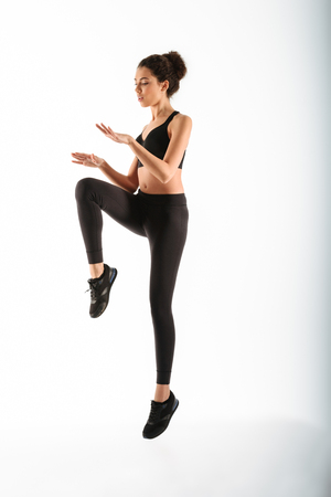 Full length image of Concentrated fitness woman jumping in studio over white background Stock Photo