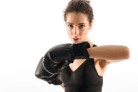 Concentrated curly brunette fitness woman trains in boxing gloves while looking at the camera over white backgroun Stock Photo