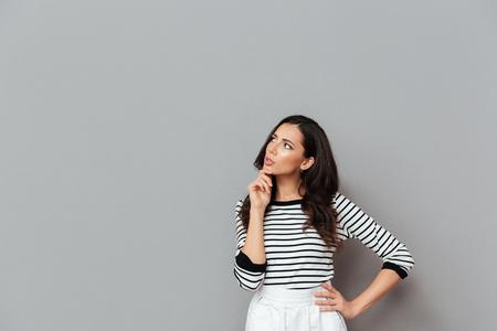 Ritratto di una donna seria che osserva via lo spazio della copia con la mano sul suo mento isolato sopra fondo grigio