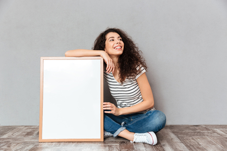 Caucasian woman with beautiful hair posing with legs crossed demonstrating big great painting or portrait, isolated over grey wall copy space