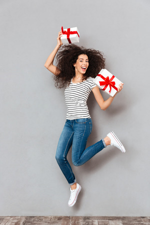 Happy emotions of positive woman in striped t-shirt and jeans enjoying lots of presents holding in hands, having fun partying over grey background