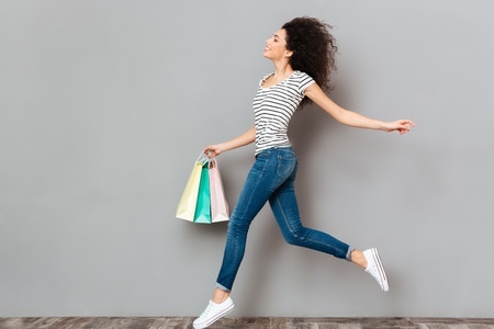 Happy emotions of wonderful female in jeans carrying a lot of purchases in hand, during shopping at sale day isolated in studio Stock Photo