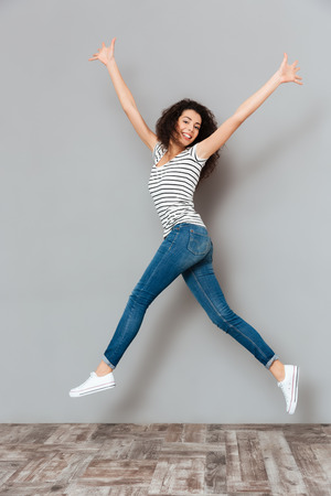 Energetic woman 20s in striped t-shirt and jeans, jumping with hands throwing up in air over grey background