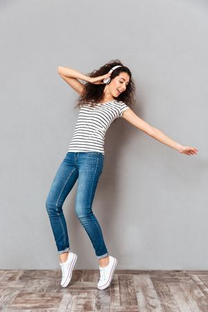 Full size view of amazing lady in striped t-shirt and jeans wearing headphones dancing and playing around, while listening sounds over grey background Stock Photo