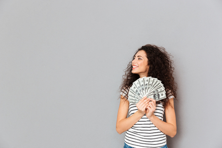 Young woman in casual holding fan of 100 dollar bills in hands looking aside with broad smile being glad, over grey wall in studio
