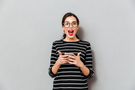 Portrait of a happy woman in eyeglasses holding mobile phone and looking at camera isolated over gray background