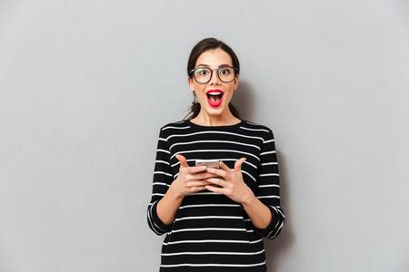 Portrait einer glücklichen Frau in den Brillen , die Handy hält und Kamera lokalisiert über grauem Hintergrund betrachtet Standard-Bild