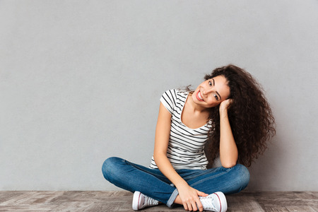 Close up portrait of curly woman in casual clothes sitting in lotus pose on the floor propping up her head with hand, being happy and candid over grey wall
