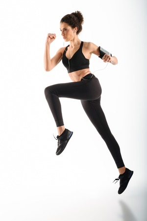 Full length image of Concentrated curly brunette fitness woman running in studio and listening music over white background Stock Photo