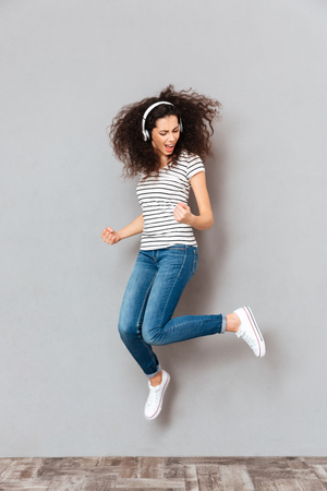 Full size view of playful female dancing and partying with waving hair against grey background, while listening music in earphones