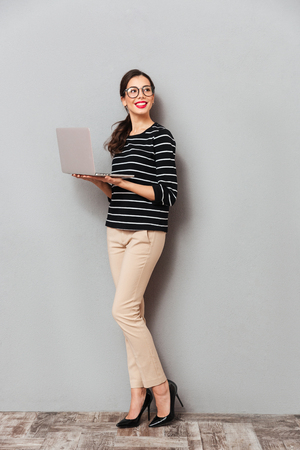 Full length portrait of a happy woman in eyeglasses holding laptop computer and looking away at copy space isolated over gray background