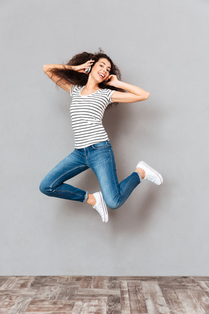 Full size view of beautiful woman in casual being in good mood levitating with pleasure because listening to favourite music in earphones, over grey wall Stock Photo
