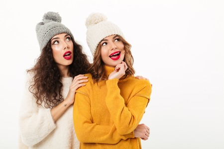 Two intrigued girls in sweaters and hats standing together while looking away over white background Stock Photo